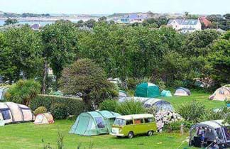 fields with tents and blue sky at la vaugrat campsite in guernsey