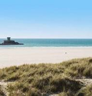 white sand and blue sea and sky at st Ouen's bay in jersey