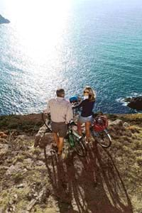 a couple with bicycles looking over the sea in jersey channel island