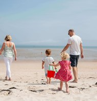 a family walking along the golden sands on a beach in jersey