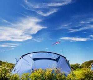 tent outside with blue sky and green grass guernsey channel islands