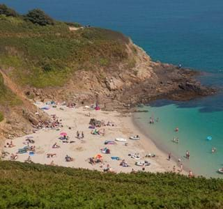 white sand with people enjoying the beach at guernsey channel islands