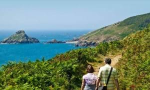romantic couple holding hands and walking through sark channel islands