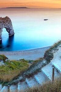view with clifftop and golden sands with blue sea at durdle door dorset