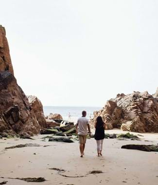 plemont beach couple walking through guernsey