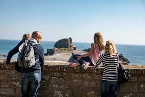 A family of 4 look out over Hermitage Rock from Elizabeth Castle in Jersey