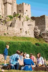 family looking up at mont orgueil jersey castle