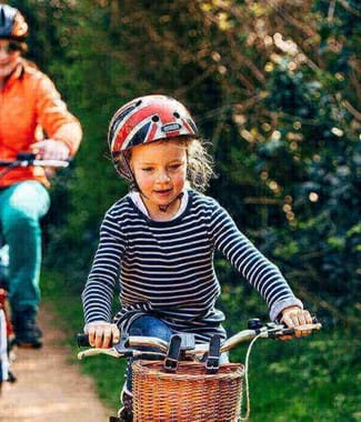 little girl cycling with family behind on cycle path