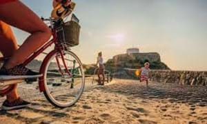 person cycling by fort grey guernsey sand
