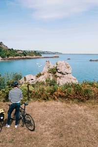 couple with bikes looking over jersey channel island sea