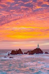 jersey corbiere lighthouse with orange pink sky