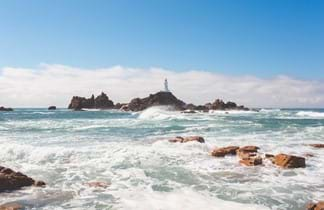 corbiere lighthouse in a blue sea at jersey channel islands