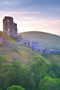 view of corfe castle dorset with green countryside and beautiful sky