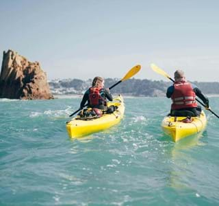 a couple of kayaks in the water in jersey channel islands