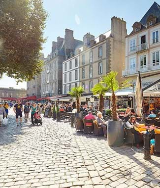 st malo street with people sitting outside eating in the sun