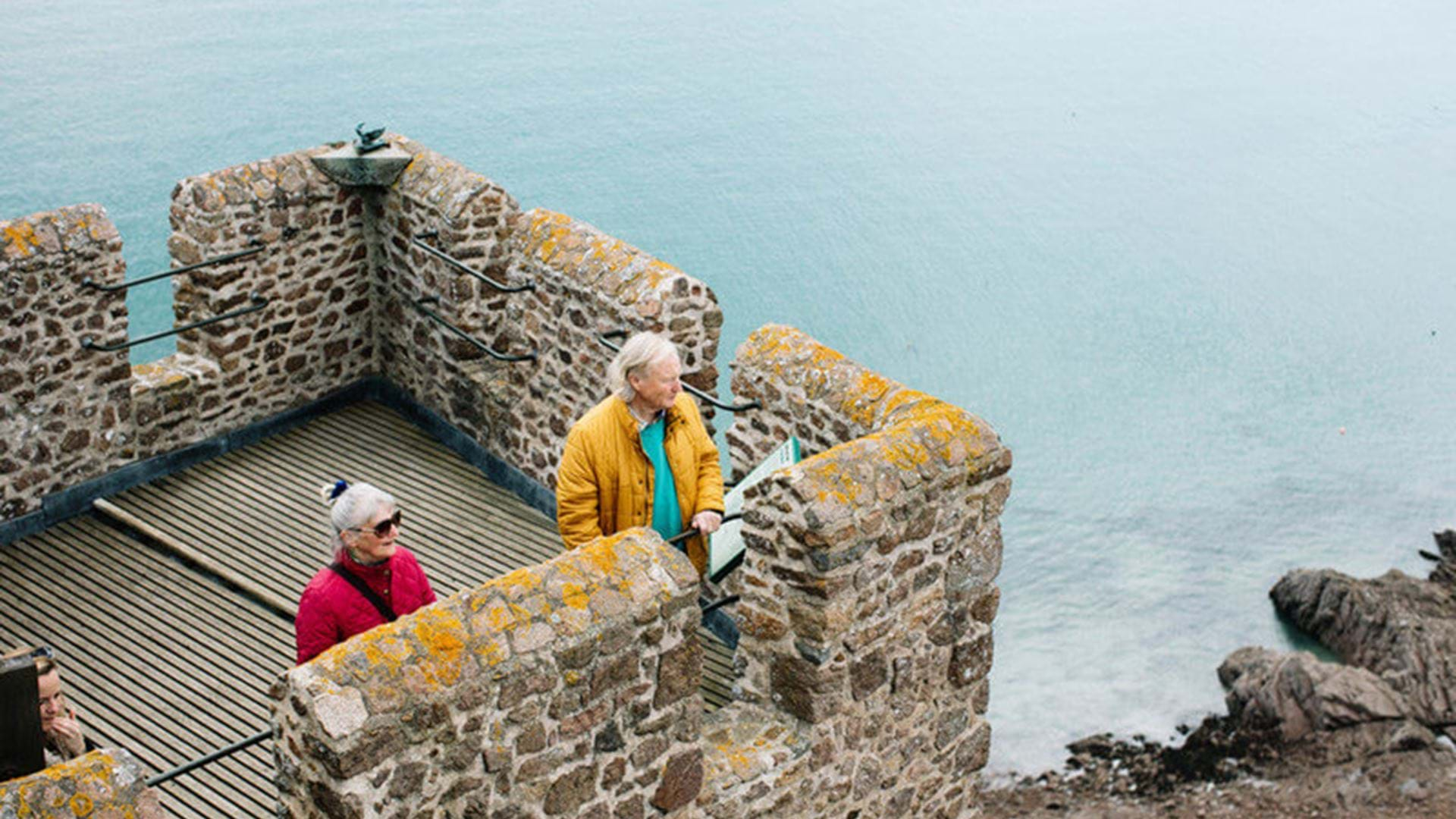 couple-looking-over-view-at-mont-orgueil-jersey-channel-islands