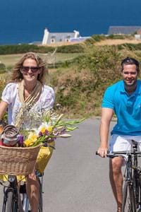 a couple cycling in the sun on the road in guernsey