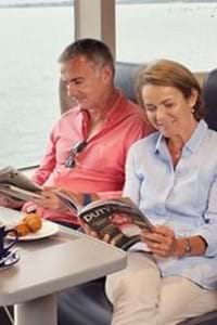 couple sitting and reading magazine in club class onboard condor rapide
