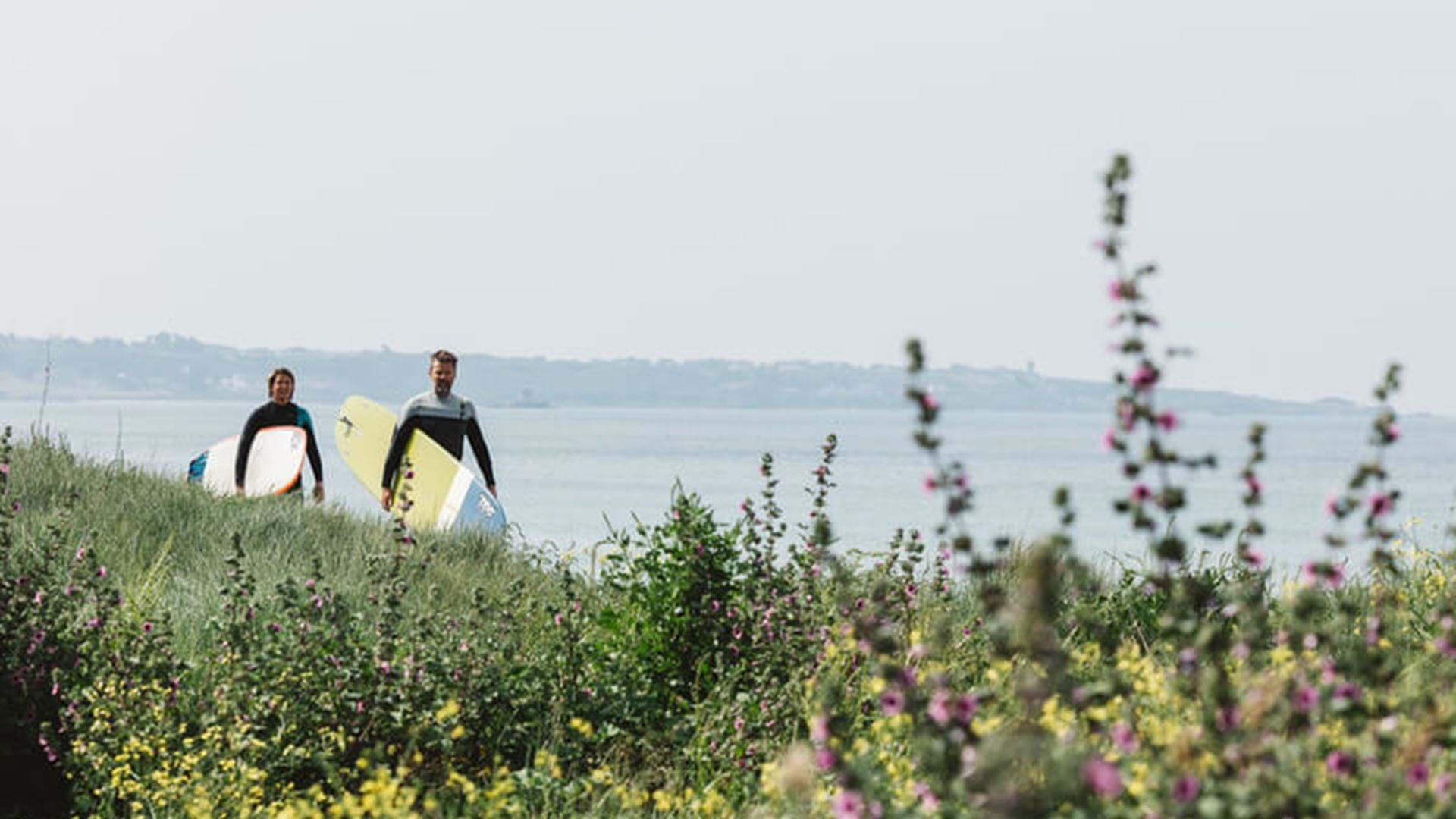 two-surfers-walking-in-st-ouens-bay-jersey