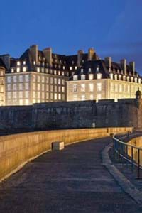 beautiful walls of st malo lit up at night with blue black sky in background