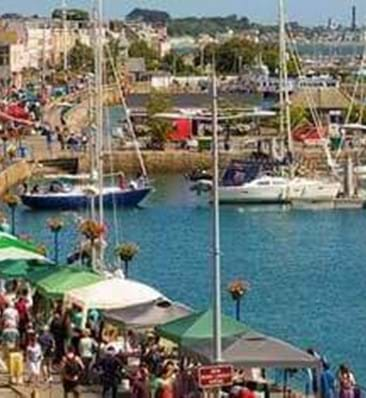 stalls and shopping with boats in the sea outside st peter port