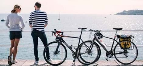 couple with their bicycles looking over sea in jersey channel islands