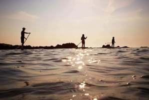 people paddleboarding guernsey on sunlit sea