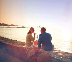 couple sitting on rock looking over guernsey sea channel islands