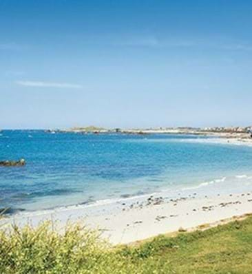 view of cobo bay in guernsey with white sand and green grass