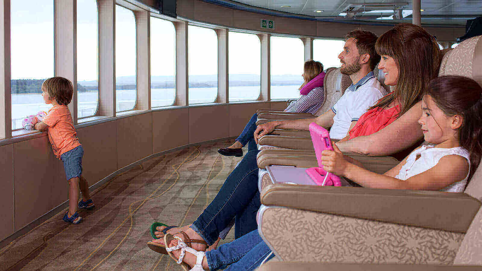 family sitting in the front seats looking at the view in horizon lounge condor